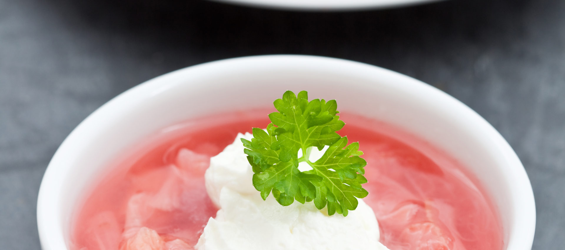 Stewed rhubarb with yogurt in a white dish on a slate background