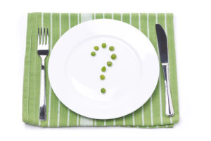 empty plate with green peas in the shape of a question mark, con
