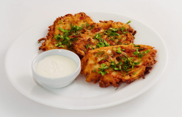 Plate of fried brown vegeterian potato pancakes with cup of cream isolated at white background. Nationail Russian meal.